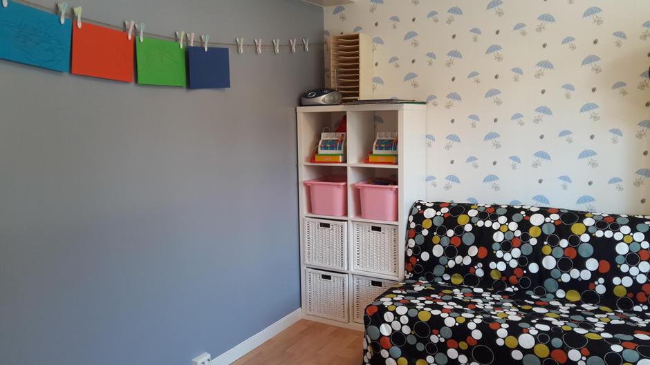 Bildet viser en sofakrok i Tåsenveien med tegninger på veggen og en hylle med leker