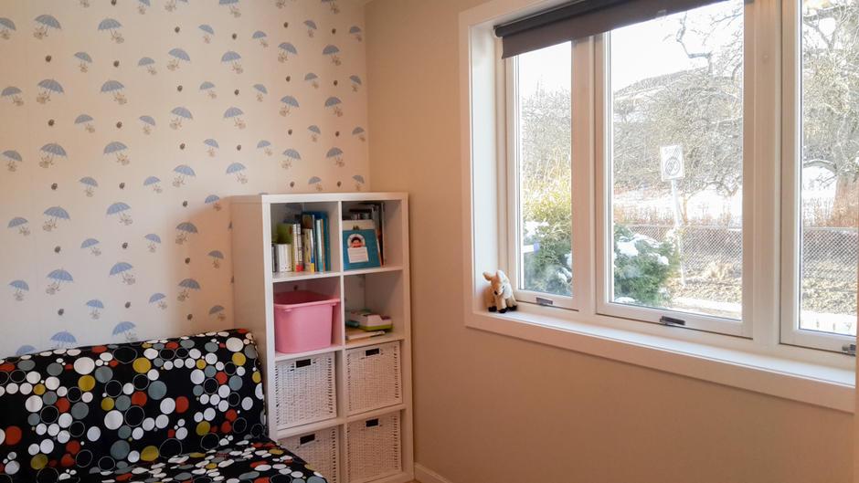 Bildet viser sofa, leker, hylle, bøker og vindu mot uteplass
