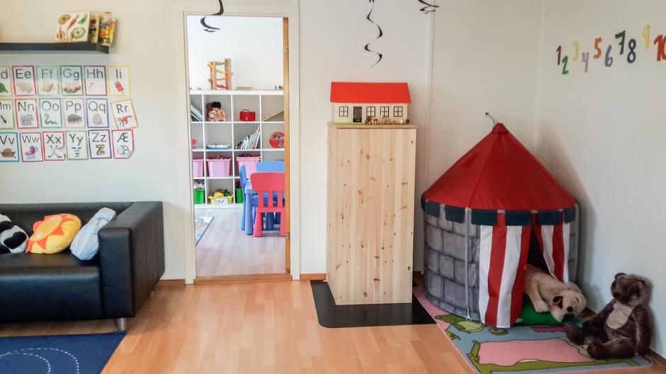 Bildet viser stue og lekerom med leker, telt, tegninger, bondegård, kosedyr