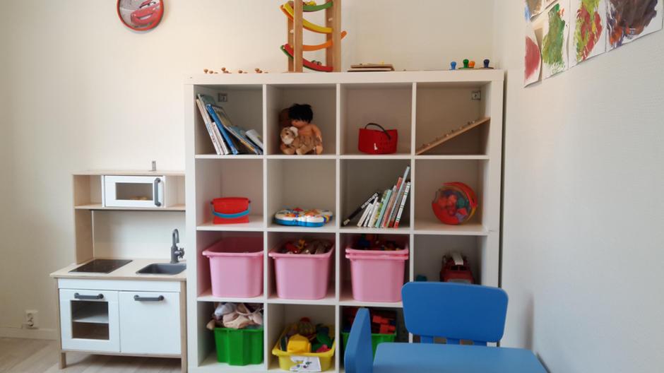 Bildet viser leker, hylle, bøker, malerier, lekekjøkken, biler