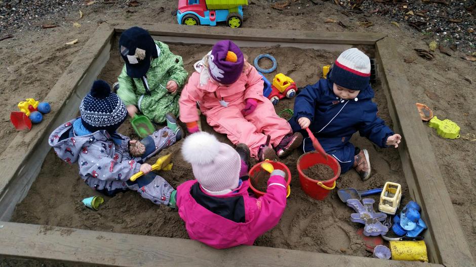 Barna sitter konsentrert og leker i sandkassen.