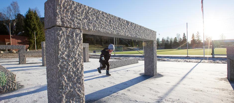 Et barn løper mellom steinskulpturer på en steinlagt plass.