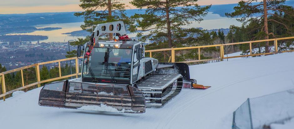 Bilde av en preppemaskin som kjøre på snøen og merker opp skispor.