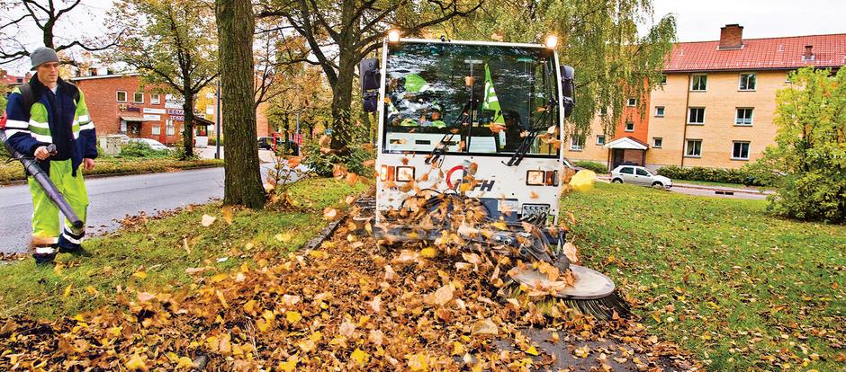 Et arbeidskjøretøy kjører på en grønn plen og koster opp høstblader.