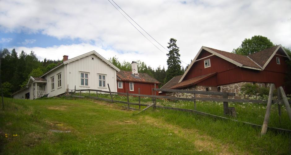 Bånkall gård med rødt fjøs og hvite hus.