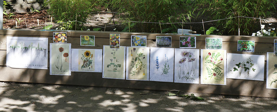 Hagen med prosjektkring, blomster og kunstverk.