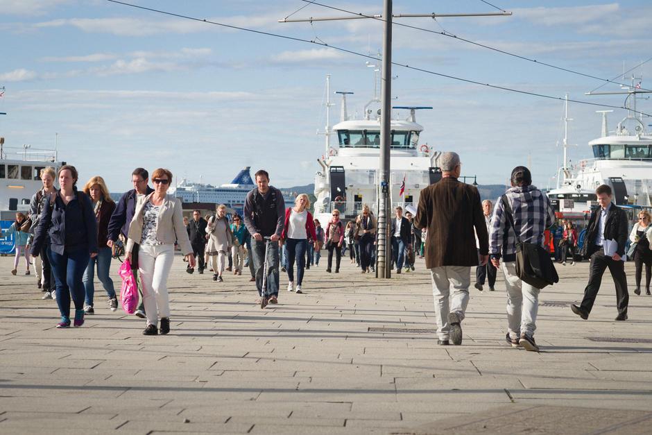 Stemningsbilde, folk på vei forbi Nesoddbåtene ved Aker Brygge.