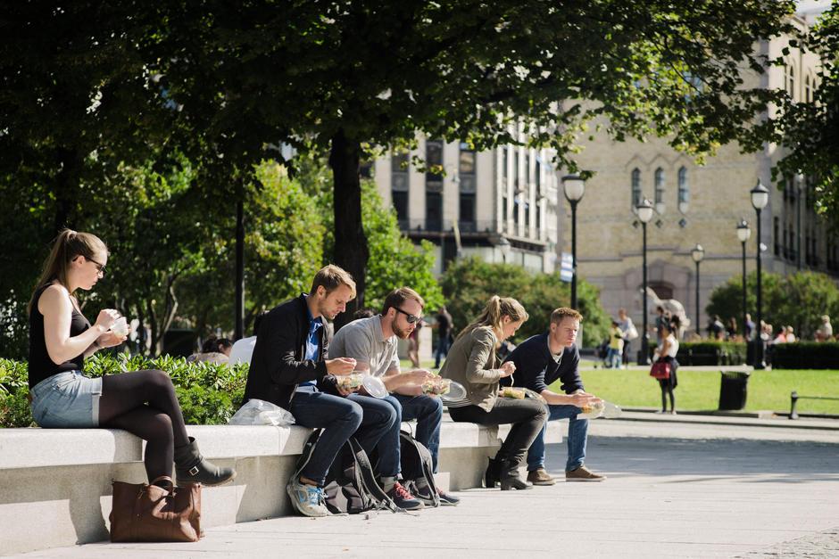 Stemningsbilde, folk spiser lunsj i sola utenfor Stortinget.