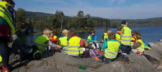 Bilde av mange barn med barnehagevester som sitter sammen på svaberg ved Sognsvann.