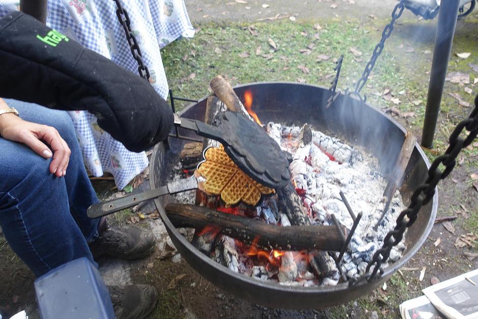 Det stekes vafler med et gammeldags vaffeljern på bålpanne