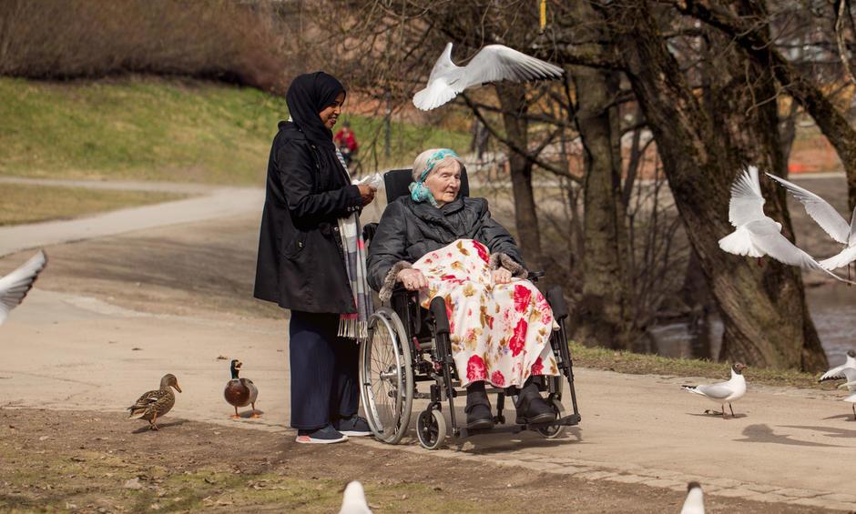 Beboer i rullestol er på tur med ansatt langs Akerselva med måker og ender som ivrige tilskuere.