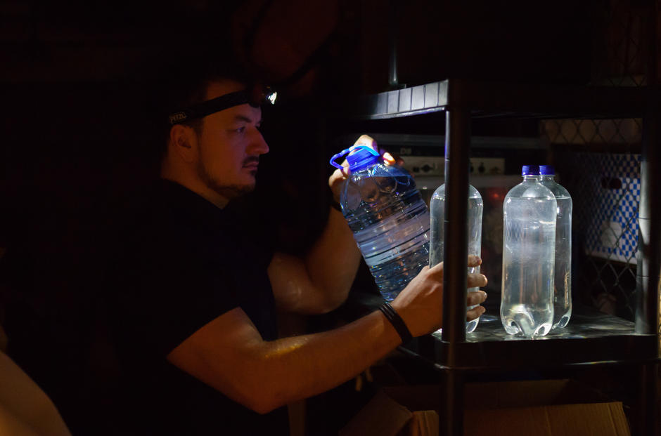 Bildet viser en person med hodelykt som henter vann i en mørk bod.