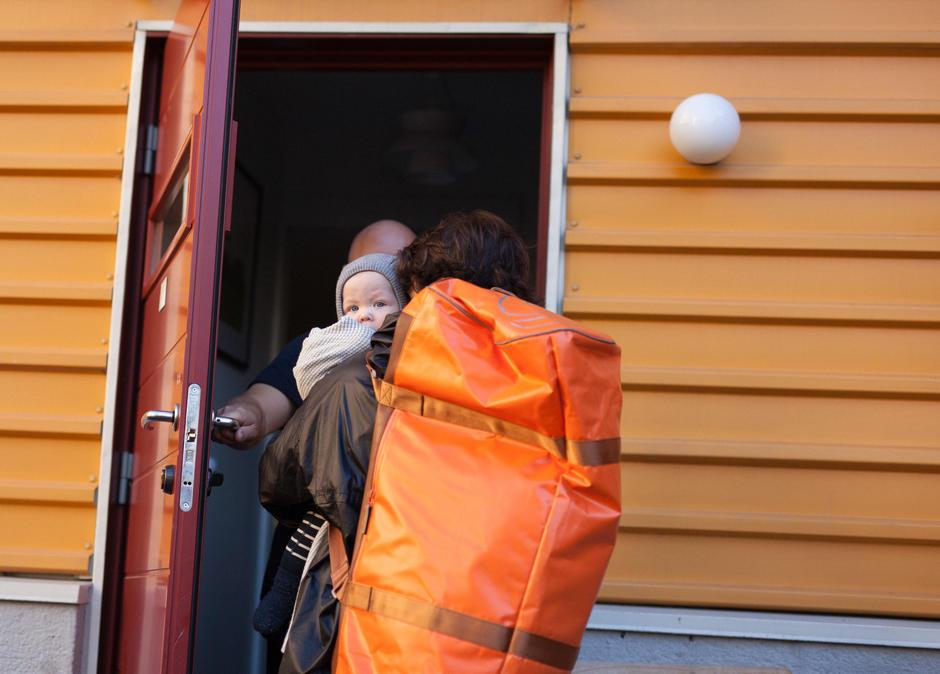 Bildet viser en person som åpen ytterdøren for en annen med barn og bagasje.