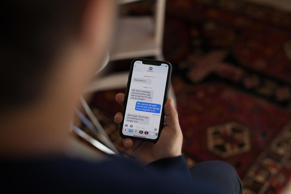 Person leser en SMS-samtale på mobiltelefonen.