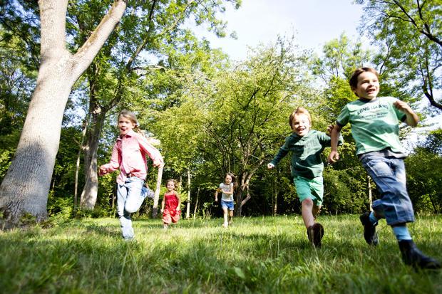 Barn som løper i gresset.