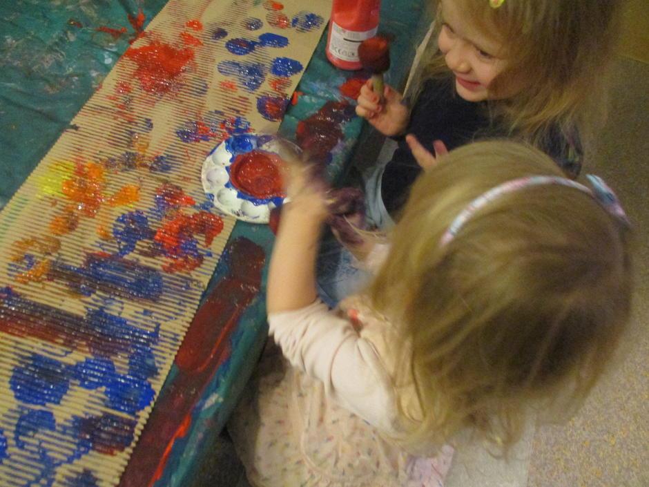 To jenter leker med maling langs malebordet