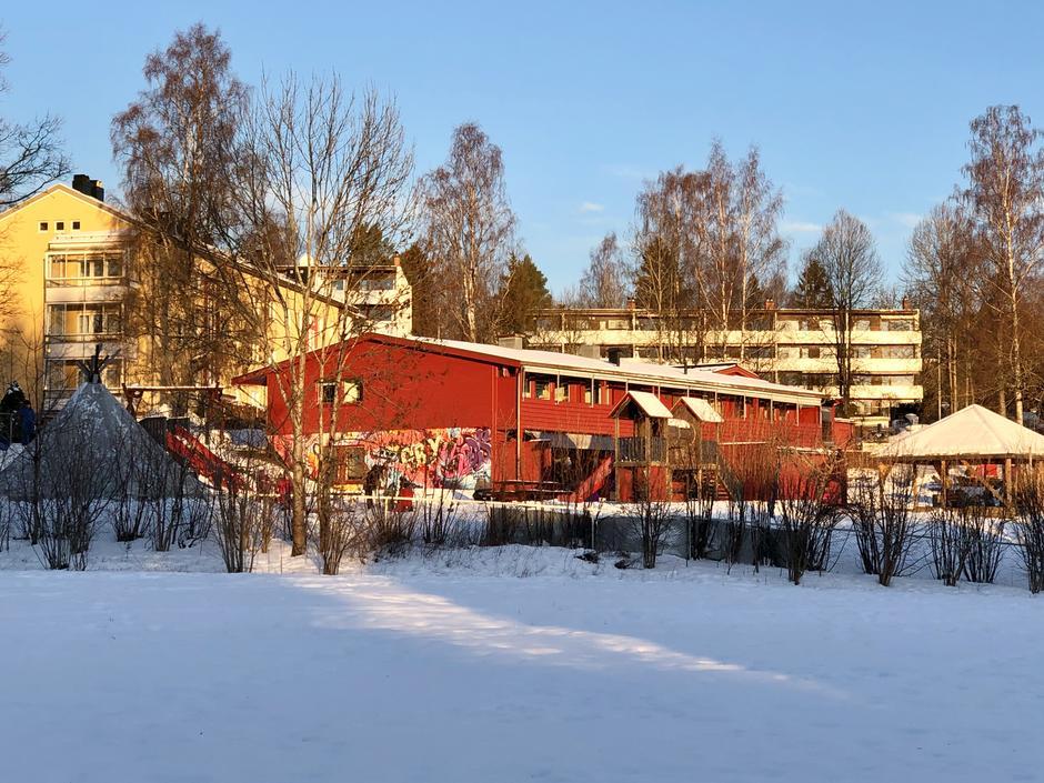 Rød bygning med og sandkasse med tak. Lavvo i barnehagen. Lekeplass.