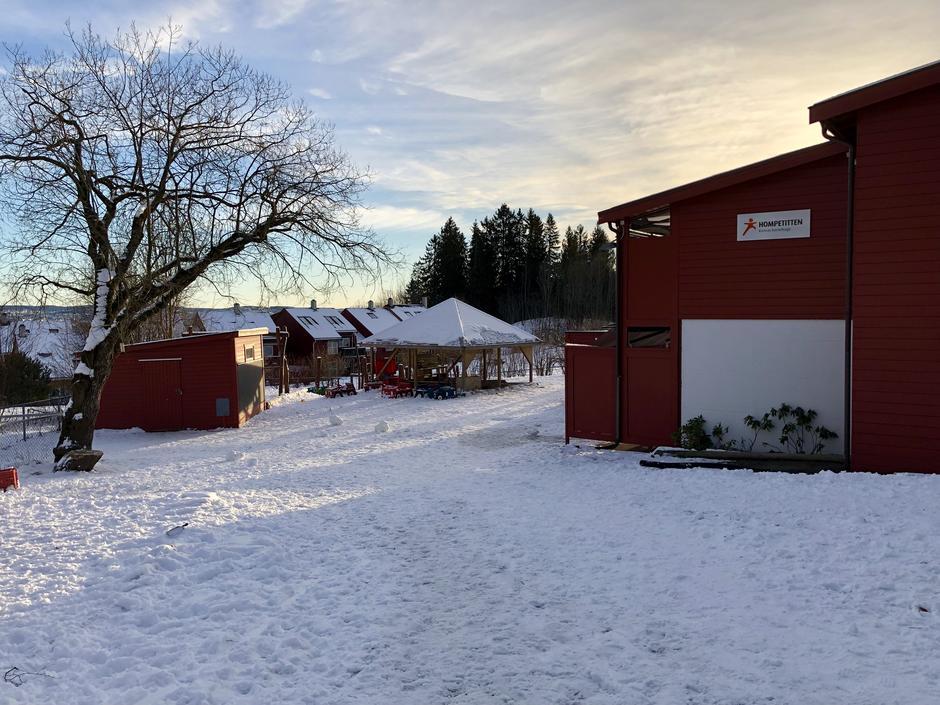 Rød bygning med skilt og sandkasse med tak, ute plassen på vinteren foran barnehagen.