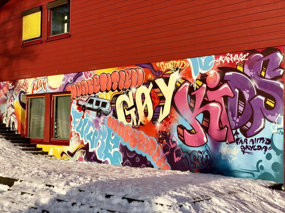 Graffitivegg med ordene gøy, kidz og figurer av en buss, en kirke og vindu.