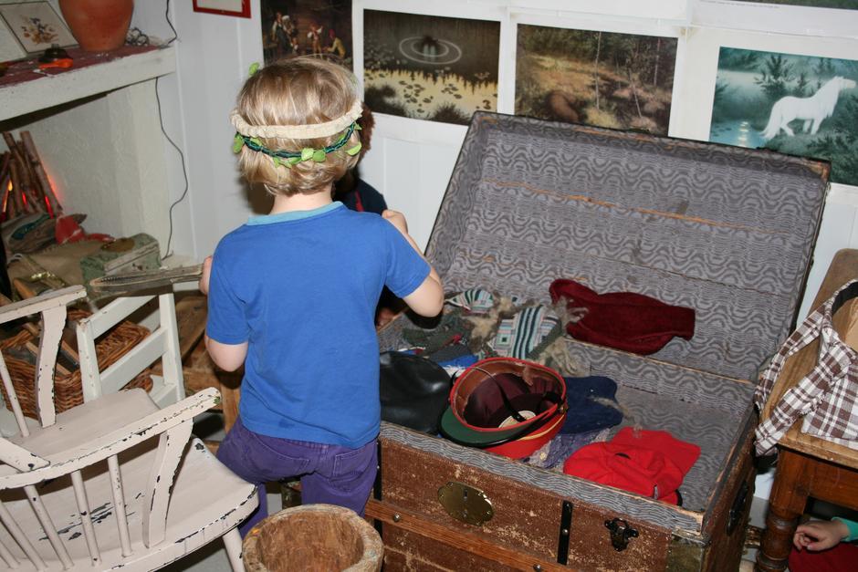 Barn ser etter utkledningstøy og rekvisitter i en kiste