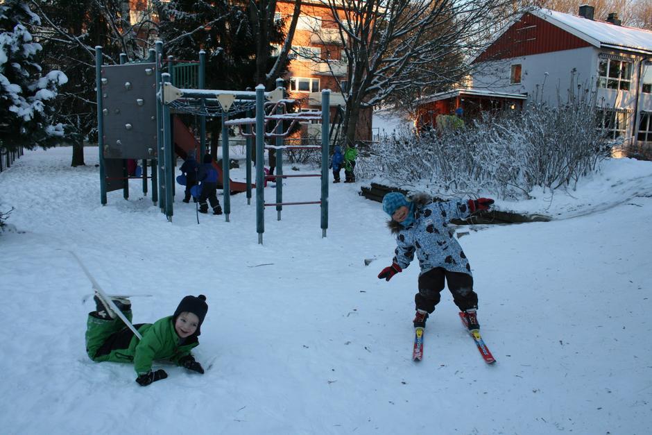 Barn på ski. Den ene detter og ler.