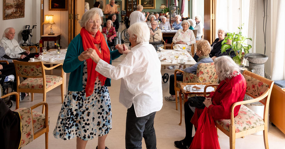 To eldre damer danser i en dagligstue