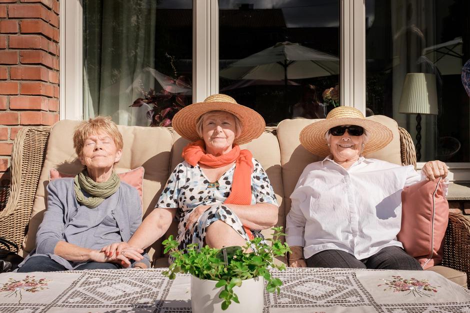 Tre eldre damer nyter solen på en krakk i hagen.