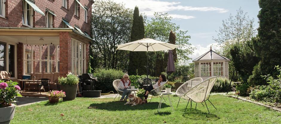 To damer sitter ved kaffebord i den grønne hagen sammen med en hund