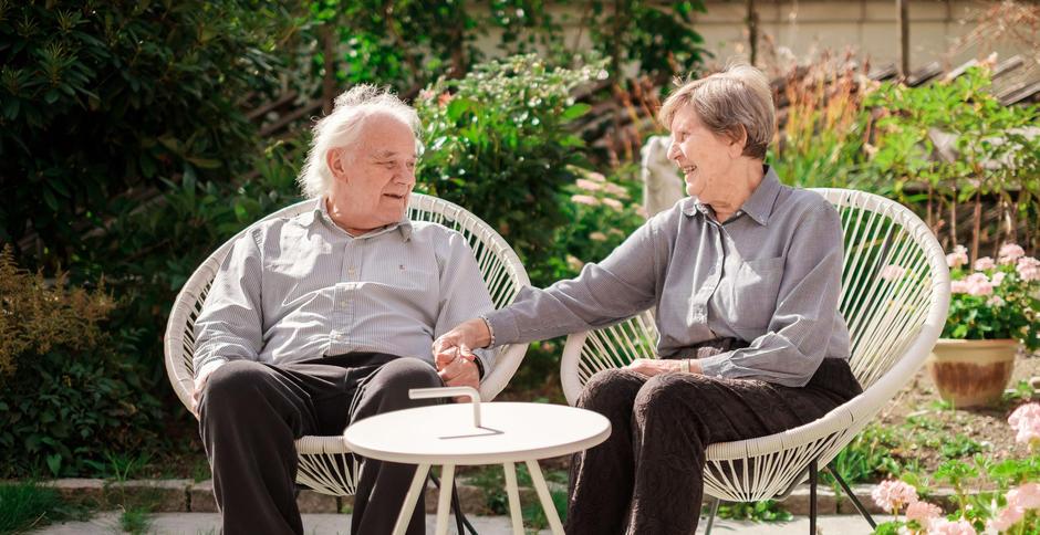 En eldre dame sitter og holder i armen til en eldre mann som sitter på nabostolen i hagen.