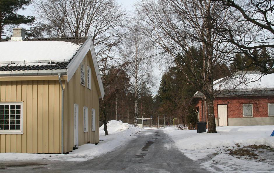 Vinterbilde av Stubberud nordre gård. Et lite trehus og et lite murhus.