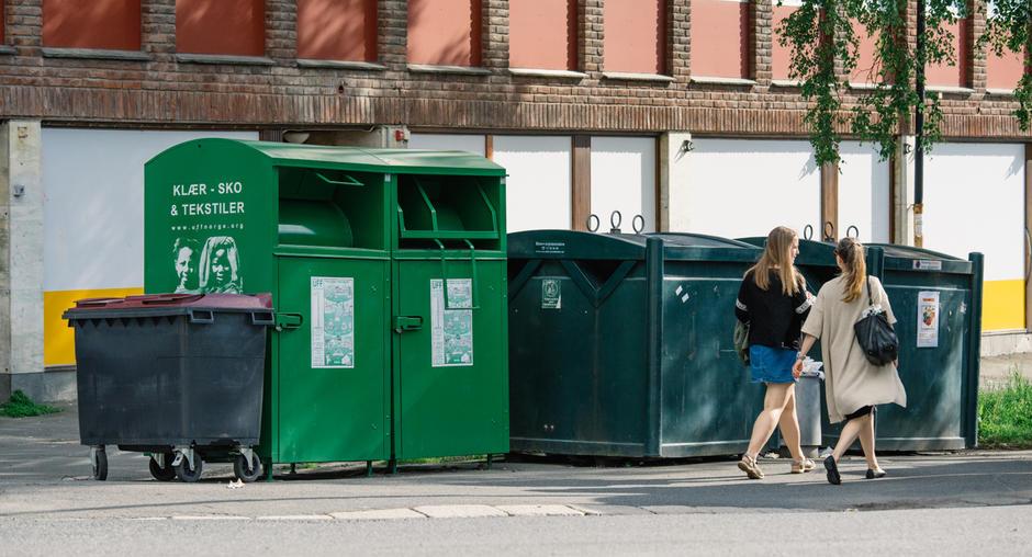 Returpunkt med glass og metall, og tekstilcontainer. To kvinner passerer.