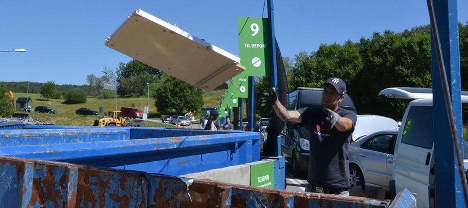 Gjenvinningsstasjon utendørs, mann som kaster materialer i en stor blå container
