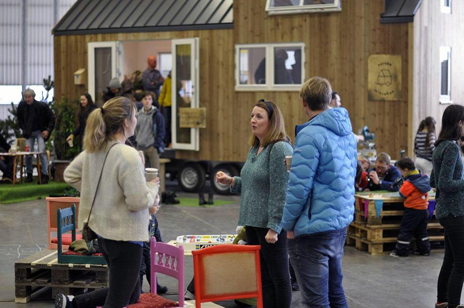 Folk innendørs på Vollebekk fabrikker. Hus på hjul i bakgrunnen.