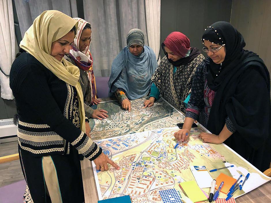 Kvinner med skaut studerer et kart på et bord.