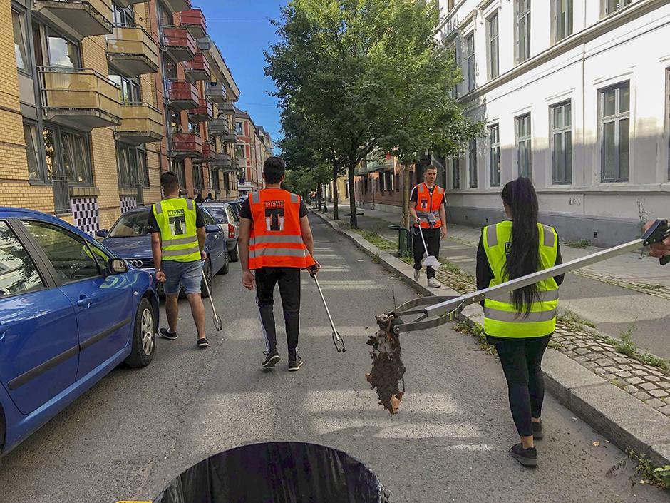 Ungdommer med gule arbeidsvester og trillebår på Tøyen.