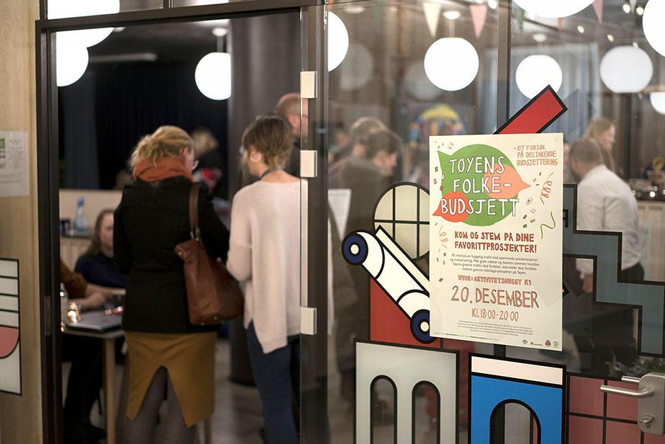 """Gruppe mennesker i rom med glassvegger, plaktat med """"Kom og stem på dine favorittprosjekter"""" på døra."""