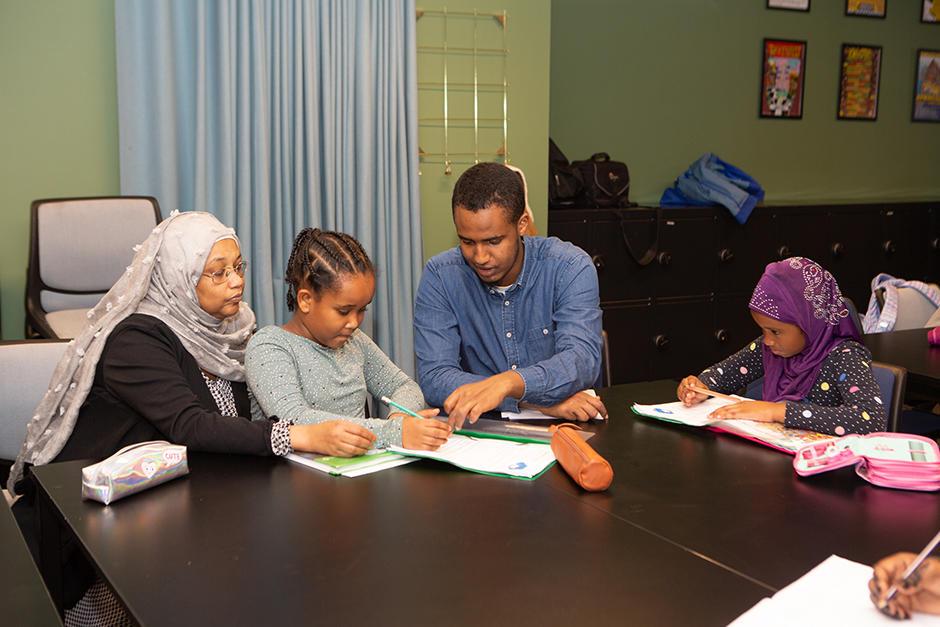 To barn og to voksne som sitter med skolebøker rundt et bord.