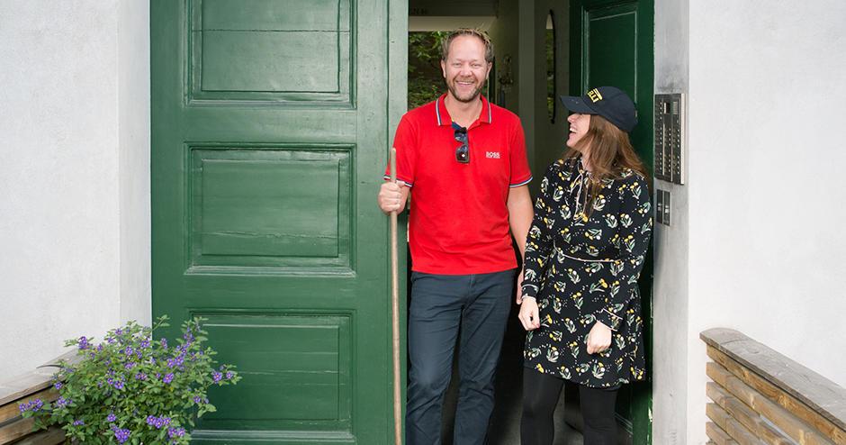 Kvinne og mann som holder en kost og smiler foran et inngangsparti.