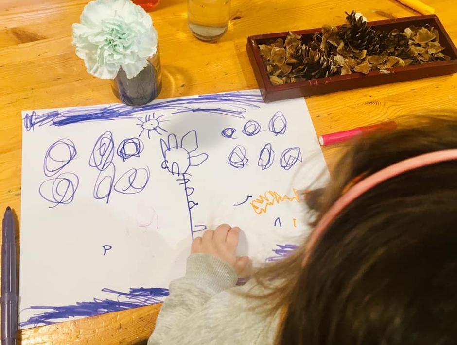 barn som tegner etter en blomst som står på bordet.