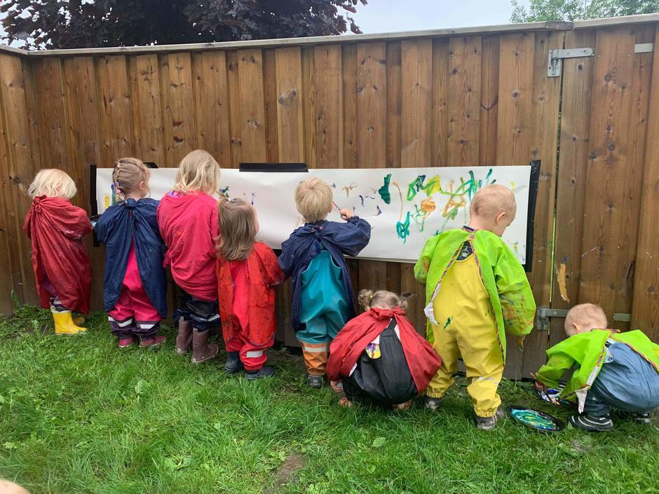 Barn som maler på et stort papir på utevegg