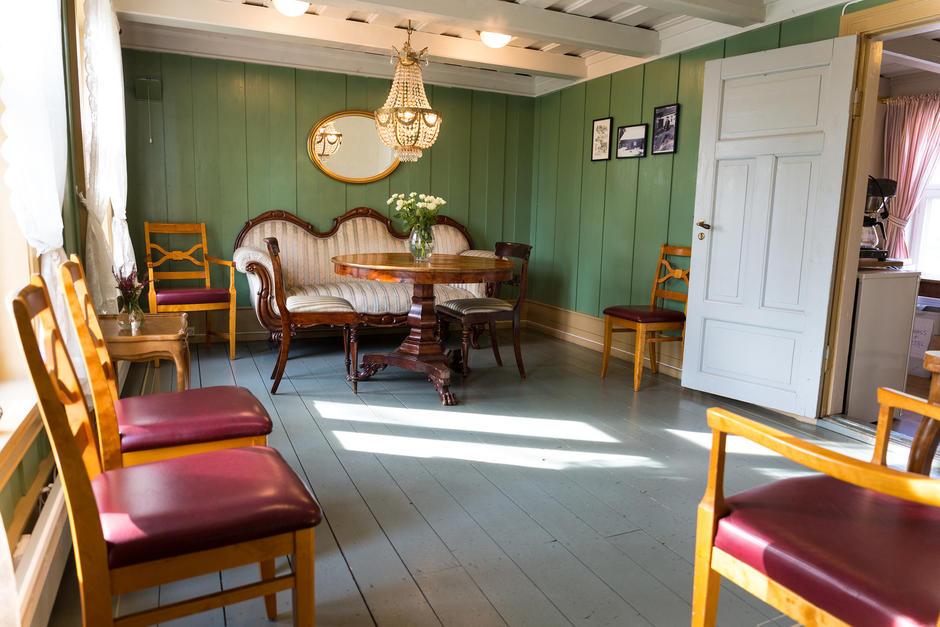 Grønt rom med rokokkosofa, lysekrone og spisestoler langs veggene.