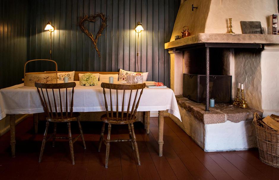 Mørkeblått rom med kjøkkenbord og stor kalkpeis.