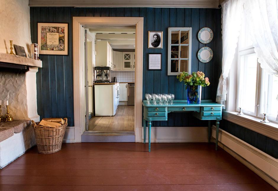 Mørkeblått rom med inngang til kjøkken med to kaffetraktere.
