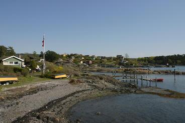 Lindøya, med strand i forgrunnen og hytter i bakgrunnen. Den nærmeste hytta er grønn og har flaggstang med flagg.