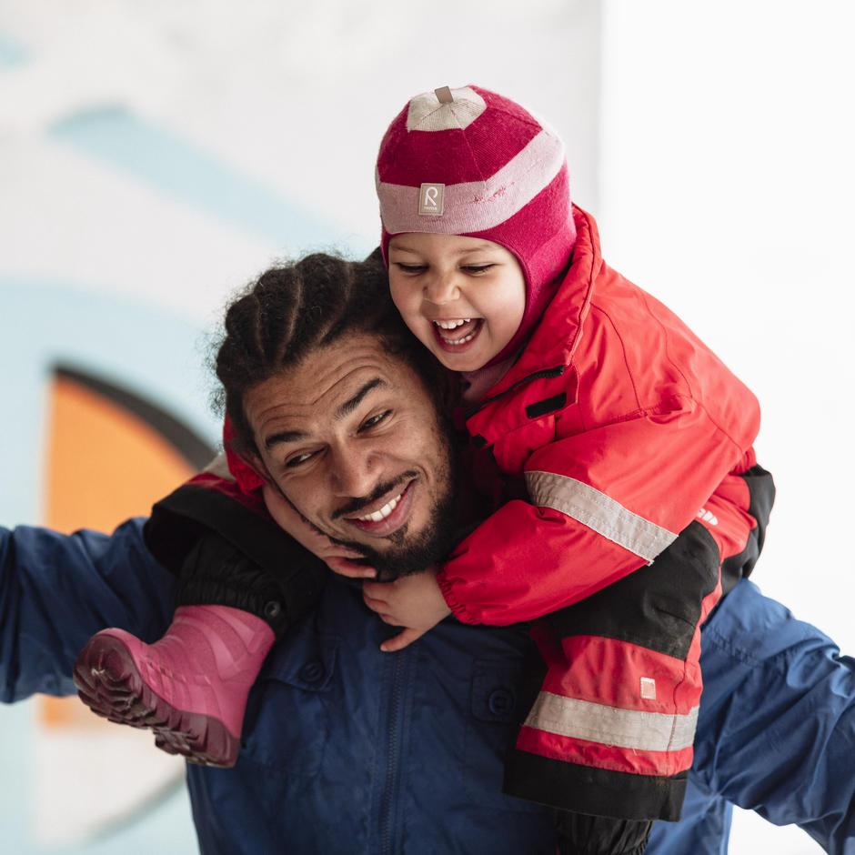 Et barn sitter på skuldrene til en voksen mann.