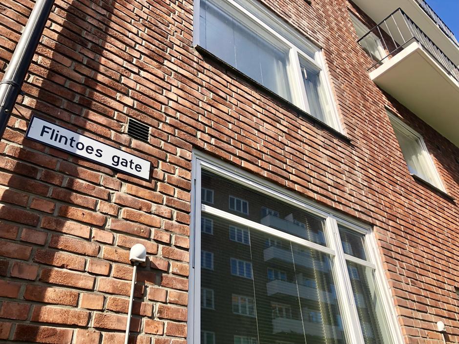 Foto av husvegg i rød mur. Hvitt gateskilt med Flintoesgate på veggen.