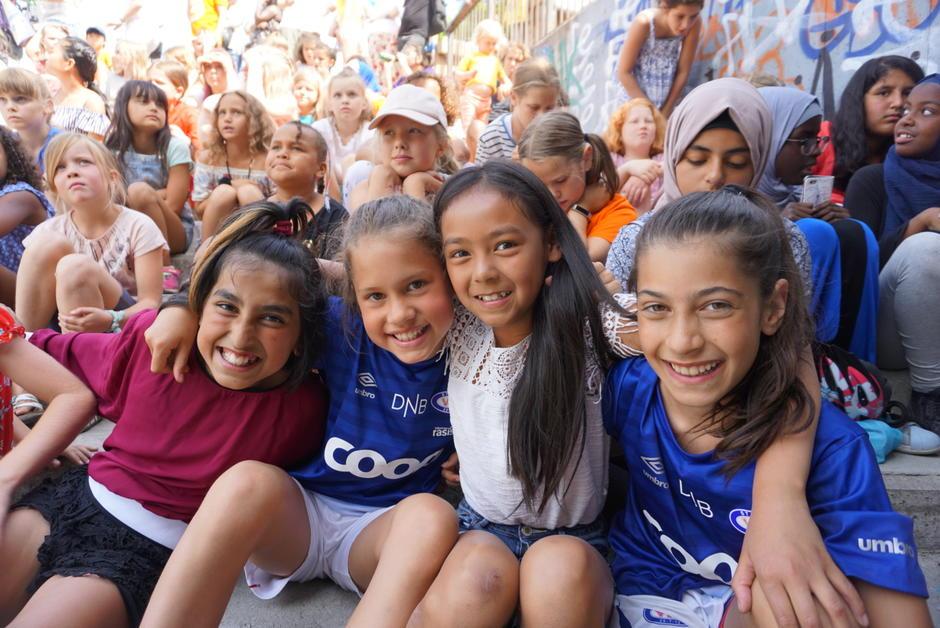Fire glade jenter som er en del av en folkemengde