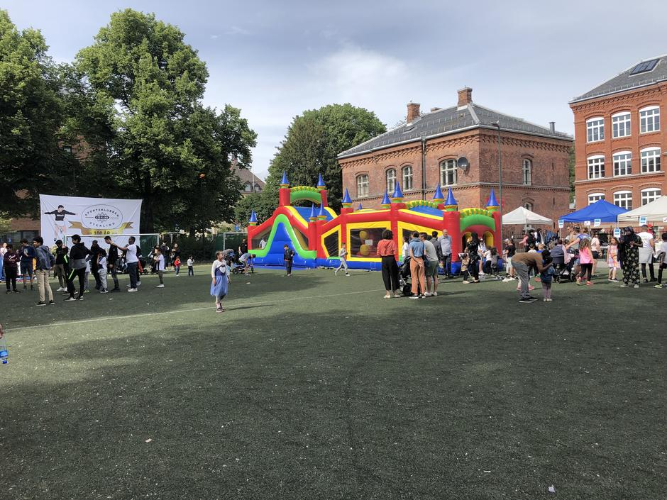 """Folk og oppblåsbart hoppeslott på Vahl skole, banner med """"Sportsklubben sterling 100 år"""""""