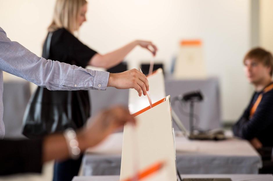 Tre personer legge stemmesedler i valgurnene. Valgmedarbeider i bakgrunn. Foto: Sturlason