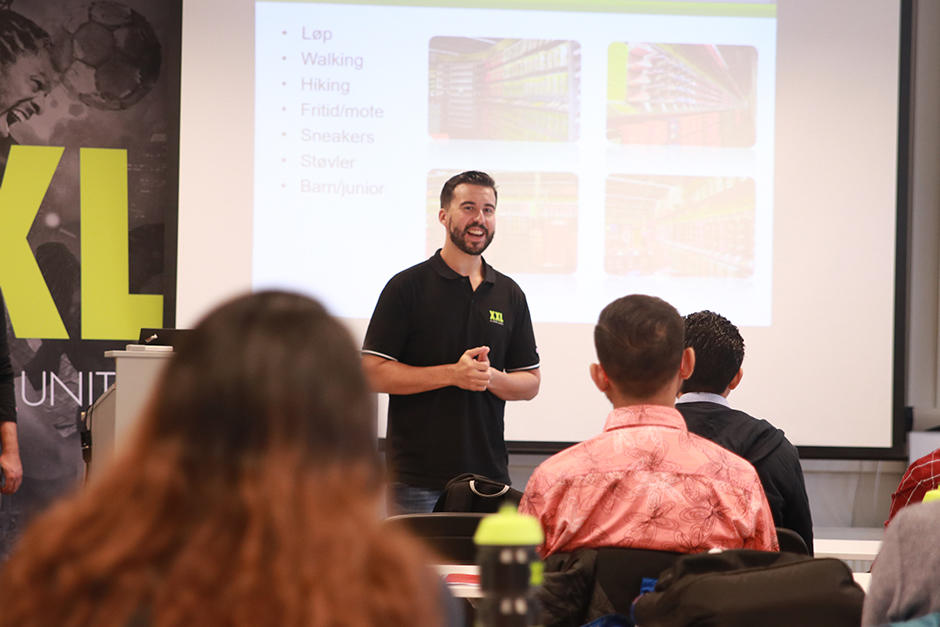 Glad mann holder foredrag foran lysbilde. XXL-logo til venstre.